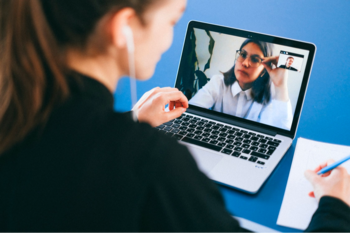 Woman making notes on video call on laptop